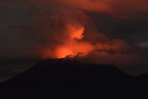 the glow of the lava lake on Nyiragongo reflects in the clouds at night