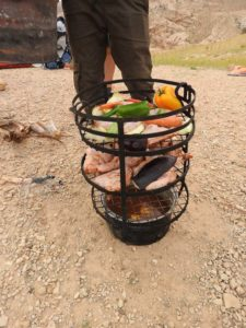 the food loaded up, ready to be covered with an oil drum and coals