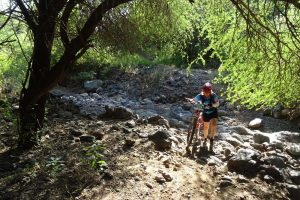 Jude pushing her bike through a rocky creek bed