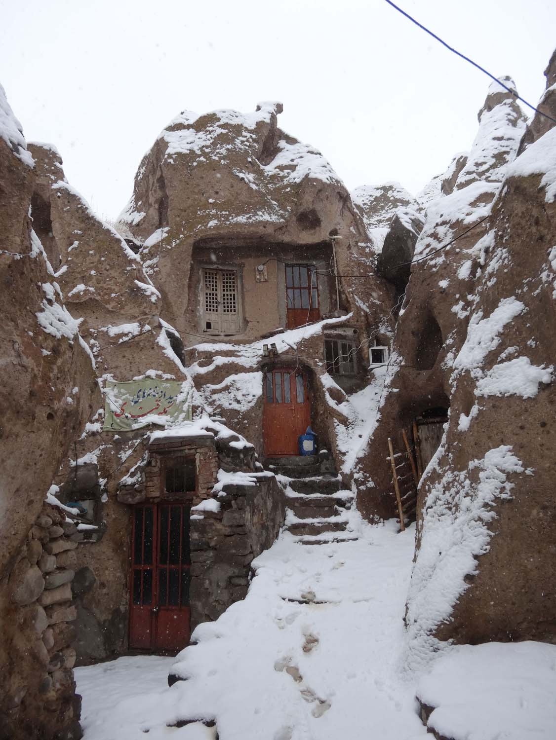 snow in Kandovan where they still live in homes made in caves
