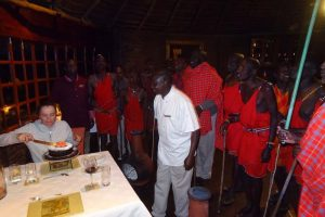 Jude cutting the cake whilst the Masai hum their sung
