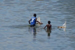 local kids playing in the river with home-made sail boats