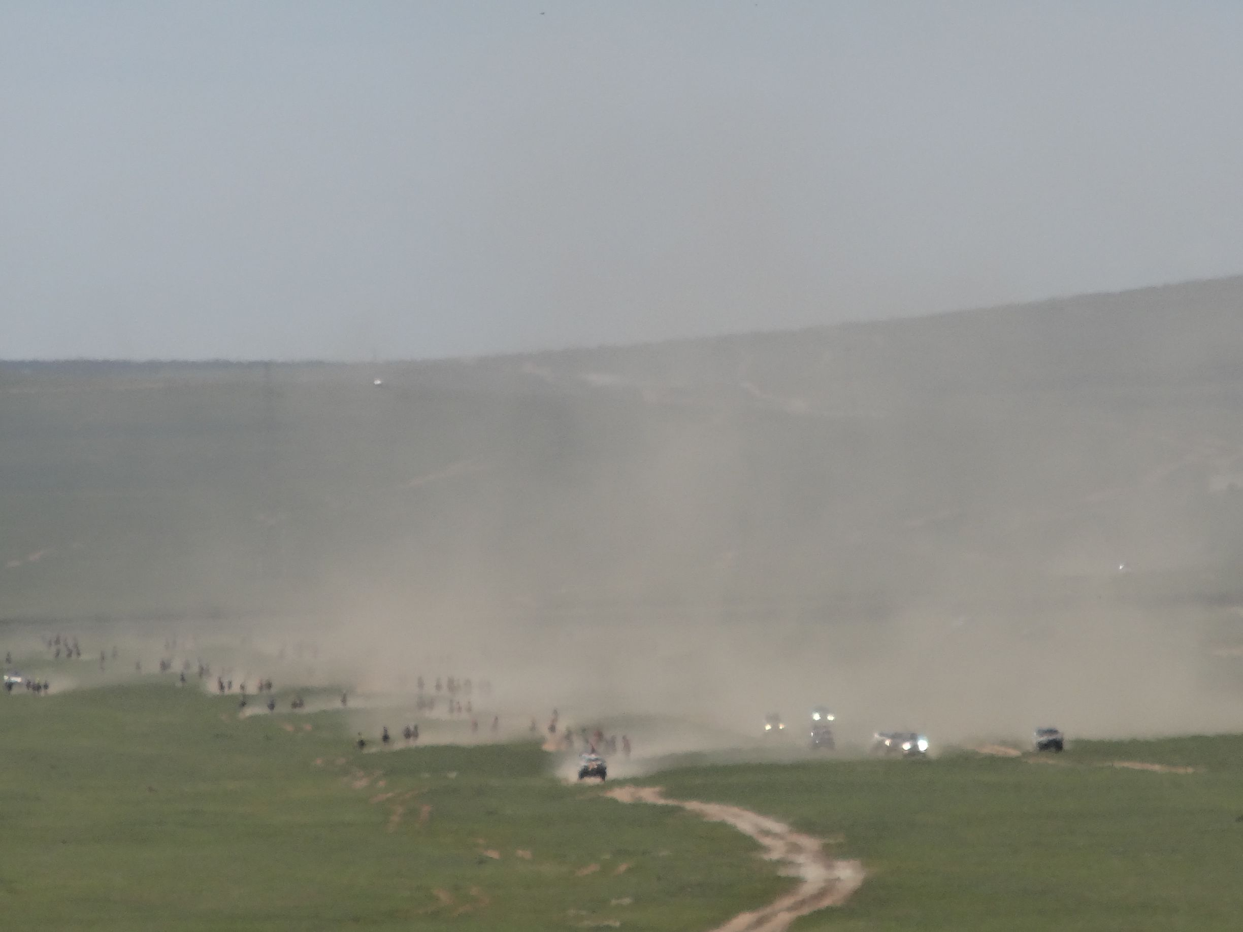 a little closer and the cloud of dust reveals horses and 4WDs