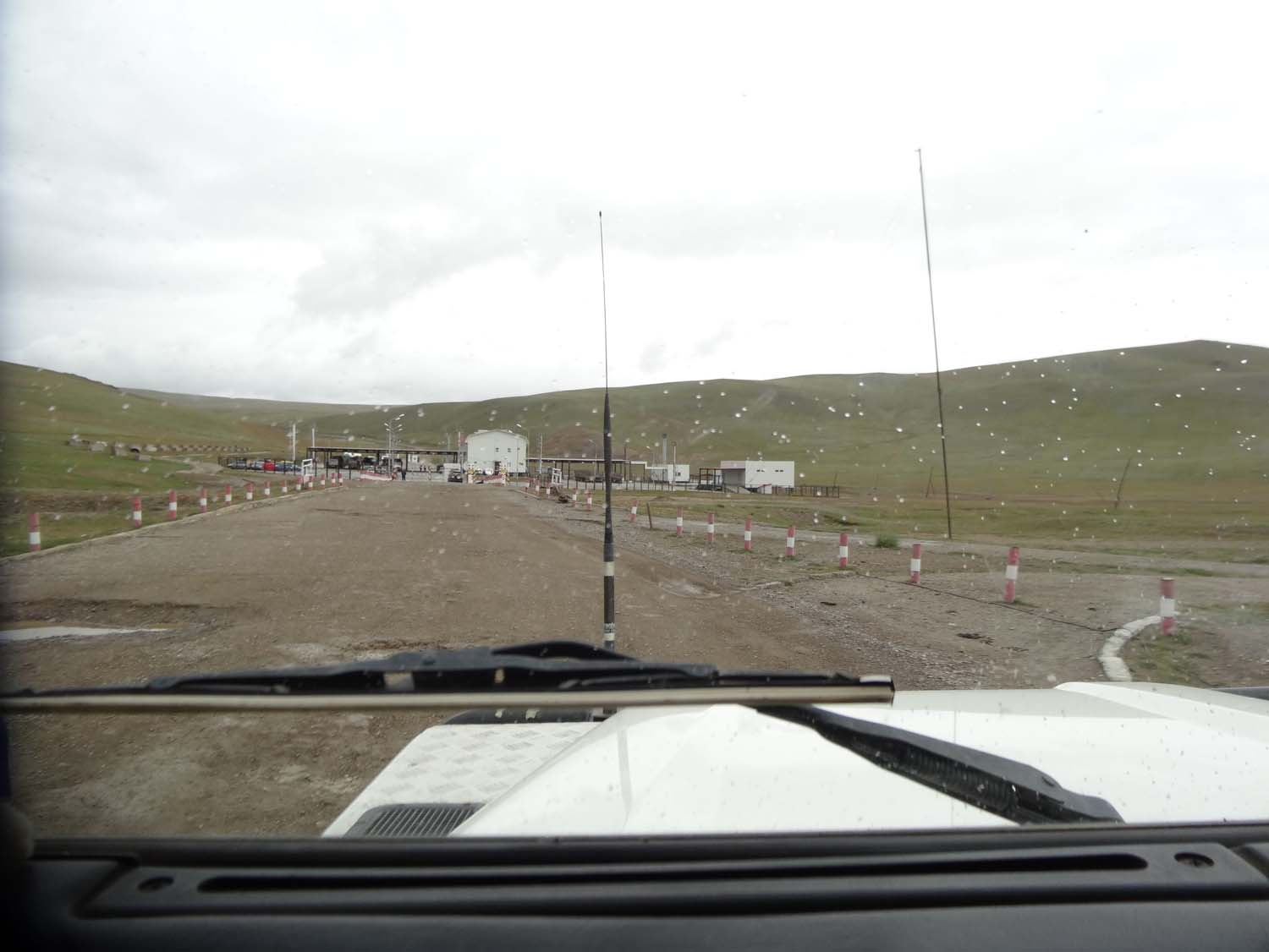 view of the Mongolian border post with the Mongol Rally people parked on the left. Leaving Mongolia you drive to the right hand side of the building and park there before entering the white building in the middle.