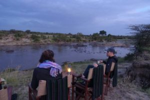 Regine and Jon enjoying sundowners at xmas, watching the hippos snort, poo and fight in the pool in the Mara River