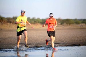 Jon and Jude running through some of the salt flats of Lake Magadi in the Shompole Marathon