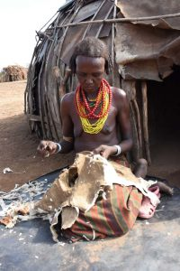 a lady from the Dasenech tribe prepares a skin