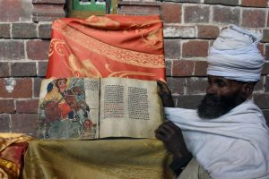 a priest proudly shows an ancient book made of animal skin in Na'akuta La'ab - a church inside a natural cave just outside Lalibela