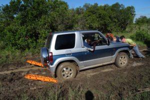 Hafiz, Katharina and Jon pushing Katharina's car out of the muddy pit