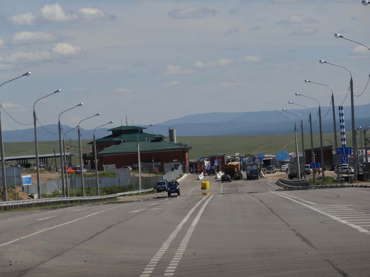 the entry gate to the border area is behind the cars and trucks parked (at the stop sign).