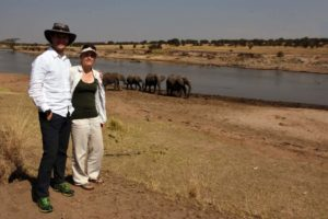 Jon and Jude next to the Mara River with a herd of elephant arriving for a drink