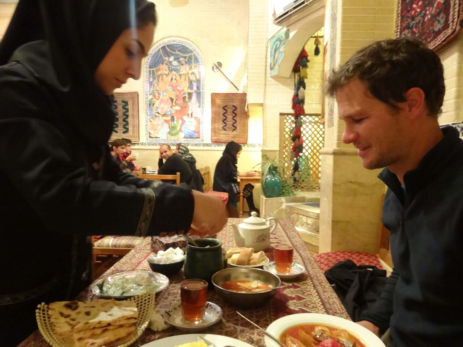 Jon getting a lesson in how to eat dizi