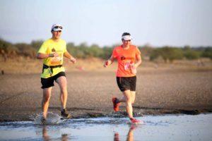 Jon and Jude running through some of the salt flats of Lake Magadi in the Shompole Marathon