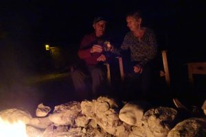 Nico and Riet enjoying a drink by the campfire at Little Oliver's camp in Tarangire